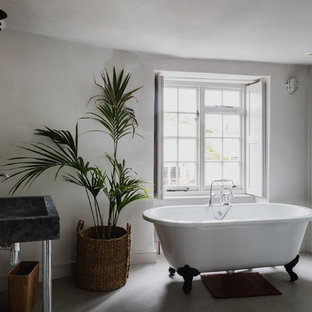 Design ideas for a medium sized traditional ensuite bathroom in London with a claw-foot bath, grey walls, grey floors and a wall-mounted sink.