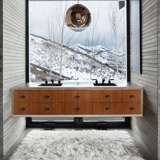 Diseño de cuarto de baño principal, contemporáneo, grande, con armarios con paneles lisos, suelo de cemento, lavabo integrado, encimera de cemento, puertas de armario de madera oscura, baldosas y/o azulejos grises, paredes grises y suelo gris