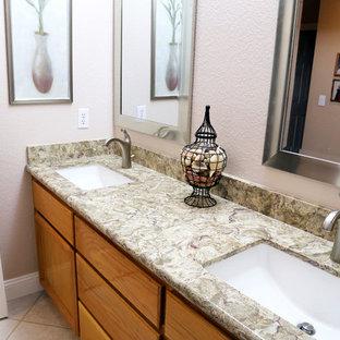 サクラメントのトラディショナルスタイルのおしゃれな浴室 (アンダーカウンター洗面器、落し込みパネル扉のキャビネット、中間色木目調キャビネット、珪岩の洗面台、ベージュのタイル、ピンクの壁、磁器タイルの床) の写真