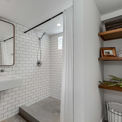 Bathroom - small industrial 3/4 white tile and subway tile concrete floor and brown floor bathroom idea in Seattle with white walls and a wall-mount sink
