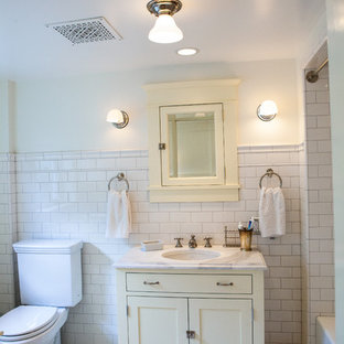 シアトルのトラディショナルスタイルのおしゃれな浴室 (アンダーカウンター洗面器、シェーカースタイル扉のキャビネット、分離型トイレ、白いタイル、サブウェイタイル、黄色いキャビネット) の写真