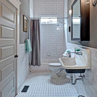Пример оригинального дизайна интерьера: ванная комната среднего размера в классическом стиле с подвесной раковиной, белой плиткой, плиткой кабанчик, серыми стенами, полом из керамической плитки, ванной в нише и душем над ванной