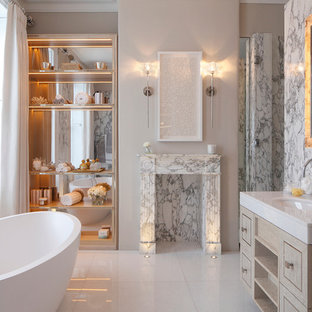 This is an example of a medium sized classic bathroom in London with a freestanding bath, a built-in sink, marble worktops, beaded cabinets and light wood cabinets.