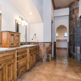 Photo of a large mediterranean ensuite bathroom in Phoenix with raised-panel cabinets, dark wood cabinets, multi-coloured tiles, stone tiles, white walls, concrete flooring, a built-in sink, tiled worktops and brown floors.
