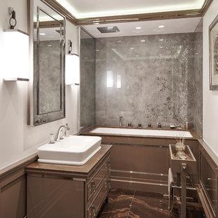 Idee per una piccola stanza da bagno padronale contemporanea con lavabo a bacinella, vasca/doccia, pareti bianche, pavimento in marmo, consolle stile comò, ante marroni e vasca sottopiano