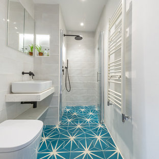 Mediterranean shower room bathroom in London with an alcove shower, white tiles, white walls, cement flooring, a vessel sink, blue floors, a hinged door and white worktops.