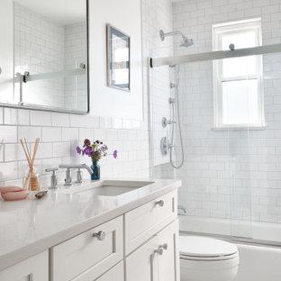 На фото: ванная комната среднего размера в стиле модернизм с фасадами в стиле шейкер, белыми фасадами, ванной в нише, душем над ванной, раздельным унитазом, белой плиткой, плиткой кабанчик, белыми стенами, полом из мозаичной плитки, душевой кабиной, врезной раковиной, столешницей из кварцита, белым полом, душем с раздвижными дверями, белой столешницей, тумбой под одну раковину и встроенной тумбой с