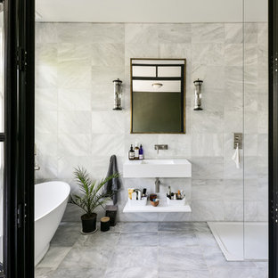 Contemporary bathroom in London with a corner shower, grey tiles, a wall-mounted sink, grey floors and an open shower.