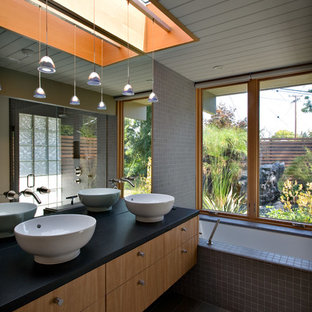 1960s master gray tile alcove bathtub photo in San Francisco with a vessel sink, flat-panel cabinets and light wood cabinets