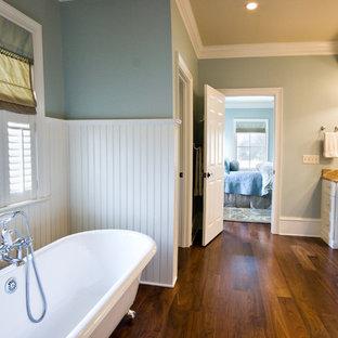 Ispirazione per una stanza da bagno tradizionale con vasca con piedi a zampa di leone, parquet scuro e pavimento marrone