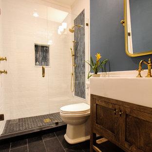 Diseño de cuarto de baño con ducha, de estilo americano, de tamaño medio, con armarios estilo shaker, sanitario de dos piezas, baldosas y/o azulejos azules, baldosas y/o azulejos blancos, baldosas y/o azulejos de cerámica, paredes azules, suelo de piedra caliza, lavabo integrado, encimera de acrílico, suelo negro y ducha con puerta con bisagras