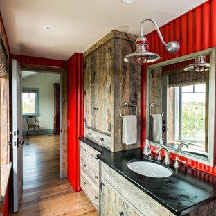 Diseño de cuarto de baño rural con puertas de armario de madera oscura, paredes rojas, suelo de madera en tonos medios y lavabo bajoencimera