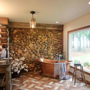 Aménagement d'une salle de bain principale montagne de taille moyenne avec une baignoire indépendante, un lavabo encastré, un placard en trompe-l'oeil, des portes de placard en bois vieilli, une douche ouverte, un WC à poser, un carrelage beige, des carreaux de porcelaine, un mur blanc, un sol en brique, un plan de toilette en stéatite, un sol multicolore, aucune cabine et un plan de toilette gris.