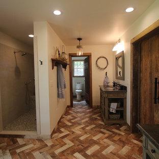 Modelo de cuarto de baño principal, de estilo de casa de campo, de tamaño medio, con armarios tipo mueble, puertas de armario con efecto envejecido, bañera exenta, ducha abierta, sanitario de una pieza, baldosas y/o azulejos beige, baldosas y/o azulejos de porcelana, paredes blancas, suelo de ladrillo, lavabo bajoencimera, encimera de esteatita, suelo multicolor, ducha abierta y encimeras grises