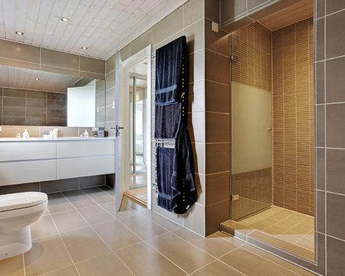 Einrichtungsidee Für Nordische Badezimmer Mit Beigen Schränken, Toilette  Mit Aufsatzspülkasten, Braunen Fliesen, Brauner