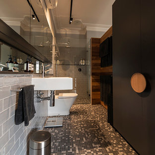 Photo of a large traditional master bathroom in Melbourne with flat-panel cabinets, black cabinets, an alcove shower, a two-piece toilet, gray tile, subway tile, grey walls, mosaic tile floors, a wall-mount sink, tile benchtops, grey floor and a hinged shower door.