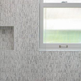 Modelo de cuarto de baño con ducha, de estilo americano, de tamaño medio, con armarios con paneles lisos, puertas de armario de madera oscura, ducha abierta, sanitario de pared, baldosas y/o azulejos grises, baldosas y/o azulejos de cerámica, paredes blancas, suelo de baldosas de cerámica, lavabo integrado, suelo gris, ducha abierta y encimeras blancas