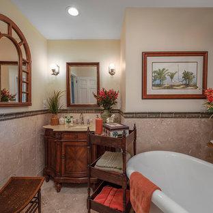 Свежая идея для дизайна: главная ванная комната среднего размера в средиземноморском стиле с фасадами островного типа, коричневыми фасадами, ванной на ножках, угловым душем, унитазом-моноблоком, бежевой плиткой, каменной плиткой, бежевыми стенами, полом из терраццо, врезной раковиной, мраморной столешницей, бежевым полом, душем с распашными дверями и бежевой столешницей - отличное фото интерьера