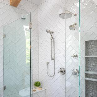 Idéer för att renovera ett mellanstort lantligt vit vitt en-suite badrum, med luckor med infälld panel, vita skåp, ett fristående badkar, en kantlös dusch, en toalettstol med separat cisternkåpa, vit kakel, keramikplattor, vita väggar, klinkergolv i porslin, ett undermonterad handfat, marmorbänkskiva, brunt golv och dusch med gångjärnsdörr