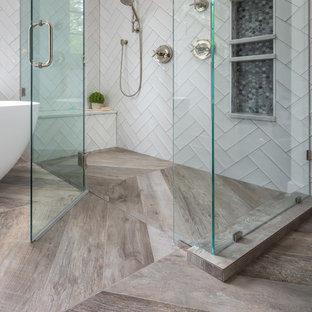 Mid-sized farmhouse master white tile and ceramic tile porcelain tile and brown floor bathroom photo in Raleigh with recessed-panel cabinets, white cabinets, a two-piece toilet, white walls, an undermount sink, marble countertops, a hinged shower door and white countertops