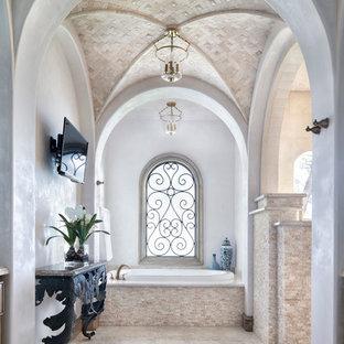 Diseño de cuarto de baño mediterráneo con bañera encastrada, baldosas y/o azulejos beige y paredes blancas