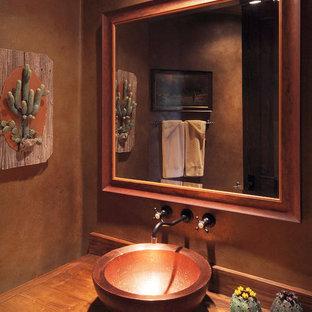 Modelo de cuarto de baño principal, de estilo americano, grande, con armarios con paneles lisos, puertas de armario de madera oscura, paredes marrones, lavabo sobreencimera y encimera de madera