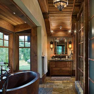 Modelo de cuarto de baño principal, rural, grande, con lavabo bajoencimera, armarios tipo mueble, puertas de armario de madera oscura, encimera de granito, bañera exenta, paredes beige y suelo de travertino