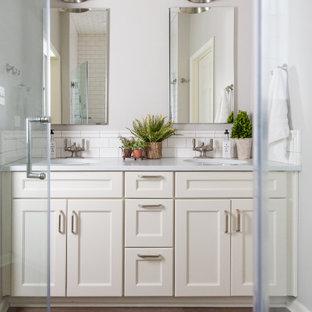 Foto de cuarto de baño principal, tradicional renovado, de tamaño medio, con armarios estilo shaker, puertas de armario beige, paredes grises, suelo de madera en tonos medios y lavabo bajoencimera