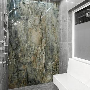 ヒューストンの中サイズのコンテンポラリースタイルのおしゃれなマスターバスルーム (グレーのタイル、フラットパネル扉のキャビネット、中間色木目調キャビネット、置き型浴槽、アルコーブ型シャワー、磁器タイル、白い壁、濃色無垢フローリング、ベッセル式洗面器、珪岩の洗面台、茶色い床、開き戸のシャワー) の写真