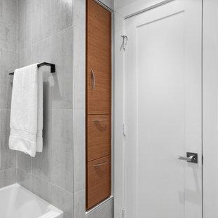 Idéer för ett mellanstort 60 tals badrum med dusch, med släta luckor, skåp i mellenmörkt trä, ett badkar i en alkov, en dusch/badkar-kombination, grå kakel, porslinskakel, grå väggar, klinkergolv i porslin, ett integrerad handfat, bänkskiva i glas, grått golv och med dusch som är öppen