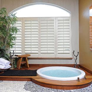 На фото: с высоким бюджетом главные ванные комнаты среднего размера в стиле фьюжн с настольной раковиной, плоскими фасадами, искусственно-состаренными фасадами, столешницей из дерева, японской ванной, инсталляцией, разноцветной плиткой, каменной плиткой, разноцветными стенами, полом из галечной плитки и угловым душем