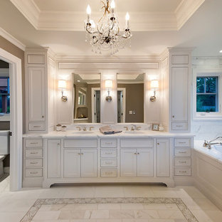 Foto di una stanza da bagno padronale classica con lavabo sottopiano, ante in stile shaker, ante bianche, top in marmo, vasca sottopiano, piastrelle bianche, piastrelle di marmo e top bianco