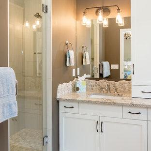 Diseño de cuarto de baño principal, de estilo americano, de tamaño medio, con armarios estilo shaker, puertas de armario blancas, ducha a ras de suelo, sanitario de una pieza, baldosas y/o azulejos beige, suelo de baldosas tipo guijarro, paredes beige, suelo de pizarra, lavabo bajoencimera y encimera de granito