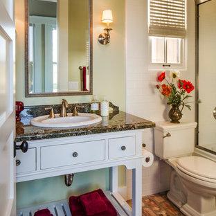 Ejemplo de cuarto de baño de estilo americano, pequeño, con sanitario de una pieza, paredes verdes, suelo de ladrillo, armarios abiertos, puertas de armario blancas, bañera empotrada, combinación de ducha y bañera, baldosas y/o azulejos blancos, baldosas y/o azulejos de cerámica, lavabo encastrado y encimera de granito