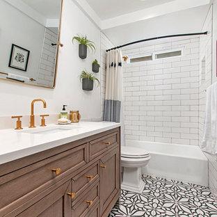 Inredning av ett klassiskt mellanstort vit vitt badrum med dusch, med luckor med infälld panel, vit kakel, tunnelbanekakel, vita väggar, klinkergolv i porslin, bänkskiva i kvartsit, skåp i mellenmörkt trä, ett badkar i en alkov, en dusch/badkar-kombination, ett undermonterad handfat, flerfärgat golv och dusch med duschdraperi