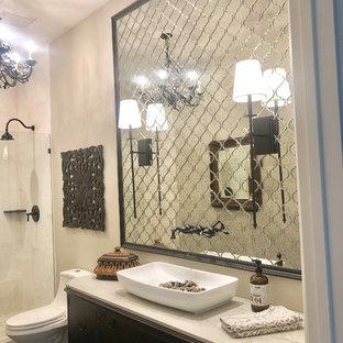 Modelo de cuarto de baño tradicional renovado, de tamaño medio, con armarios tipo mueble, puertas de armario de madera en tonos medios, ducha abierta, sanitario de una pieza, baldosas y/o azulejos beige, baldosas y/o azulejos con efecto espejo, paredes beige, suelo de madera oscura, lavabo sobreencimera, suelo negro, ducha abierta y encimeras beige