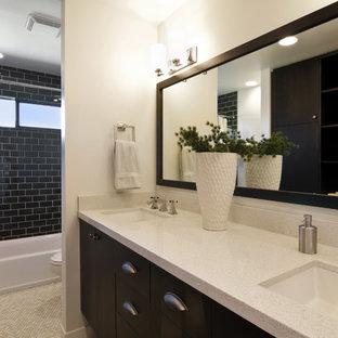Modern inredning av ett badrum, med ett undermonterad handfat, släta luckor, svarta skåp, ett badkar i en alkov, en dusch/badkar-kombination, svart kakel och tunnelbanekakel