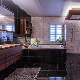 Imagen de cuarto de baño principal, contemporáneo, de tamaño medio, con lavabo encastrado, armarios con paneles lisos, puertas de armario de madera oscura, encimera de madera, bañera encastrada sin remate, ducha abierta, sanitario de pared, baldosas y/o azulejos blancos y baldosas y/o azulejos de piedra