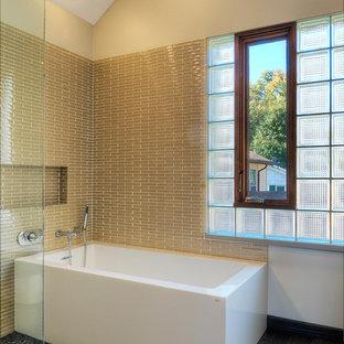 Foto de cuarto de baño principal, minimalista, de tamaño medio, con bañera exenta, baldosas y/o azulejos beige, azulejos en listel, suelo de baldosas tipo guijarro, sanitario de una pieza y paredes beige
