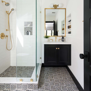 Inspiration for a transitional 3/4 white tile multicolored floor corner shower remodel in Los Angeles with recessed-panel cabinets, black cabinets, white walls, an undermount sink, a hinged shower door and white countertops