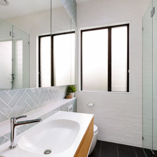 Photo of a mid-sized contemporary 3/4 bathroom in Sydney with blue tile, white tile, glass tile, ceramic floors, an integrated sink, engineered quartz benchtops, black floor, a hinged shower door, white benchtops, a single vanity, a floating vanity, flat-panel cabinets, medium wood cabinets and an alcove shower.