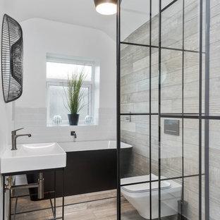 Foto di una stanza da bagno padronale industriale di medie dimensioni con vasca freestanding, doccia aperta, WC sospeso, piastrelle bianche, pareti beige, pavimento in gres porcellanato, lavabo a consolle, doccia aperta, piastrelle diamantate e pavimento beige