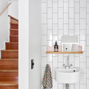 This is an example of a contemporary bathroom in Brisbane with green tile, white tile, white walls, a wall-mount sink and a single vanity.
