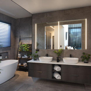 Large contemporary 3/4 bathroom in Melbourne with flat-panel cabinets, brown cabinets, a freestanding tub, gray tile, a vessel sink, grey floor, white benchtops, a niche, a double vanity and a built-in vanity.