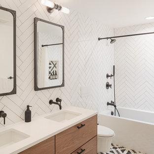 フィラデルフィアのコンテンポラリースタイルのおしゃれな浴室 (フラットパネル扉のキャビネット、中間色木目調キャビネット、アルコーブ型浴槽、白いタイル、アンダーカウンター洗面器、マルチカラーの床、シャワーカーテン、白い洗面カウンター、洗面台2つ、フローティング洗面台) の写真