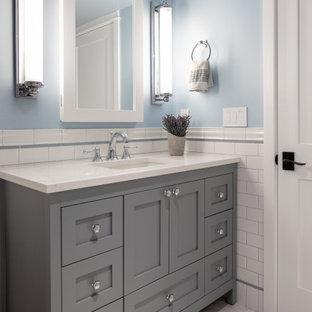 シアトルの小さいトランジショナルスタイルのおしゃれな子供用バスルーム (家具調キャビネット、グレーのキャビネット、アルコーブ型浴槽、アルコーブ型シャワー、一体型トイレ、白いタイル、磁器タイル、青い壁、磁器タイルの床、アンダーカウンター洗面器、クオーツストーンの洗面台、マルチカラーの床、シャワーカーテン、白い洗面カウンター、ニッチ、洗面台1つ、独立型洗面台、羽目板の壁) の写真
