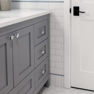 На фото: детская ванная комната в стиле современная классика с фасадами островного типа, серыми фасадами, ванной в нише, душем в нише, унитазом-моноблоком, белой плиткой, керамогранитной плиткой, синими стенами, полом из керамогранита, врезной раковиной, столешницей из искусственного кварца, разноцветным полом, шторкой для душа, белой столешницей, нишей, тумбой под одну раковину, напольной тумбой и панелями на стенах с