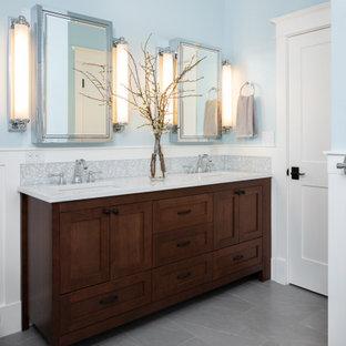 Inspiration pour une grand douche en alcôve principale traditionnelle avec un placard en trompe-l'oeil, des portes de placard en bois sombre, une baignoire indépendante, un WC à poser, un carrelage blanc, des carreaux de porcelaine, un mur bleu, un sol en carrelage de porcelaine, un lavabo encastré, un plan de toilette en quartz modifié, un sol gris, une cabine de douche à porte battante, un plan de toilette blanc, une niche, meuble double vasque, meuble-lavabo sur pied et boiseries.