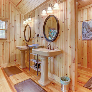 Mountain style medium tone wood floor bathroom photo in Other with brown walls and a pedestal sink
