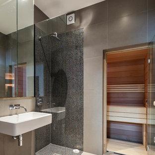 Пример оригинального дизайна: большая главная ванная комната в современном стиле с подвесной раковиной, открытым душем, серыми стенами, плоскими фасадами, серой плиткой, керамической плиткой, полом из керамической плитки и открытым душем